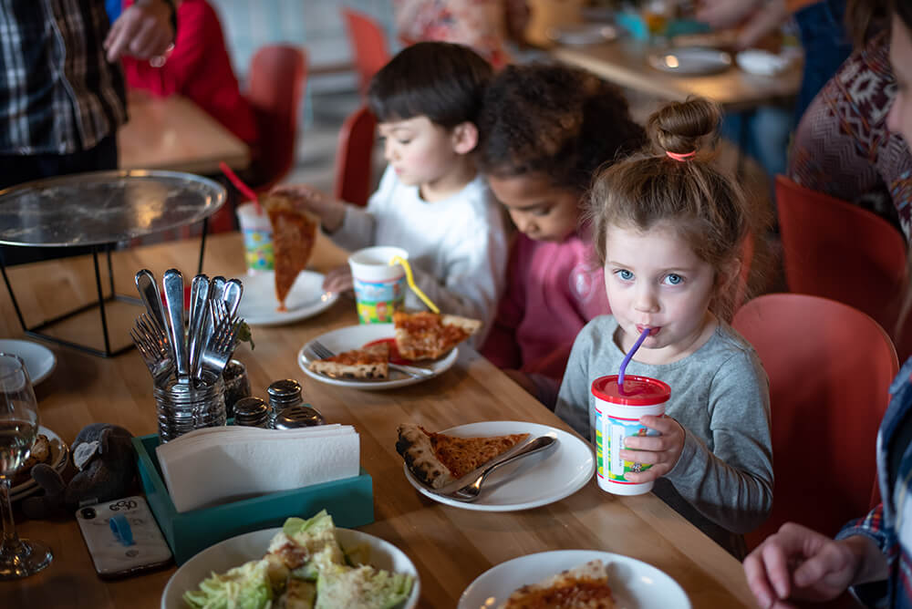 Kids enjoying pizza and drinks